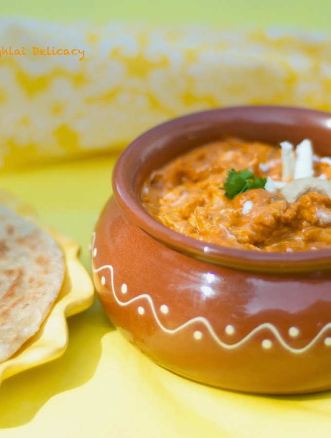 Paneer akbari in orange colored gravy, served in clay server with paratha on the side