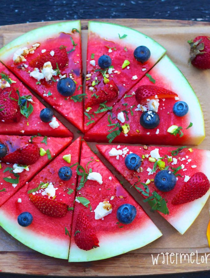 an overhead shot of Watermelon sliced like pizza topped with blueberries & strawberries feta cheese mint and balsamic vinegar on a wooden cuttingboard