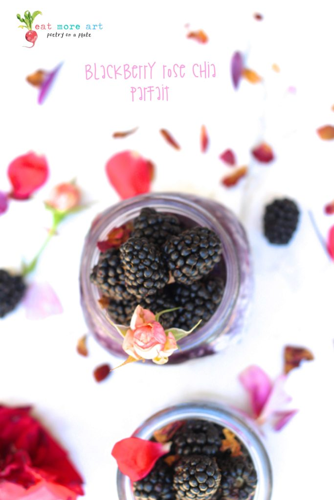 an overhead shot of blackberry rose chia parfait topped with blackberries and rose petals and rose bud on a white backdrop with flower petals and blueberries scattered