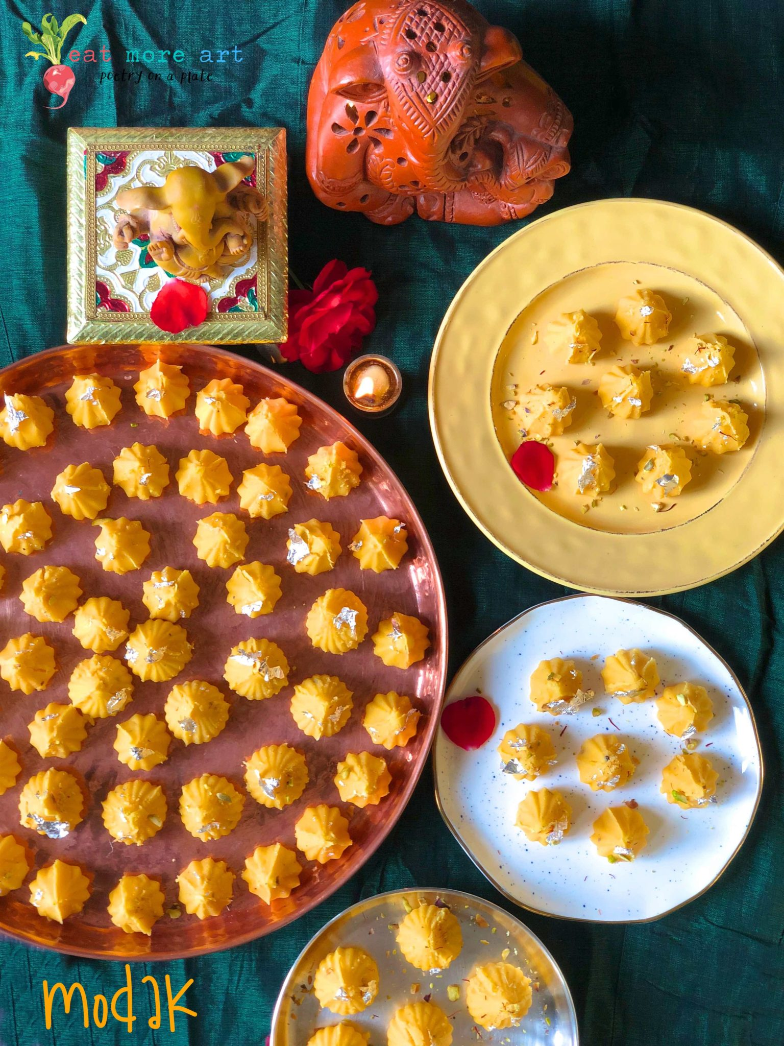 an overhead shot of Yellow color modaks on a few different platters in front of Ganesh idols