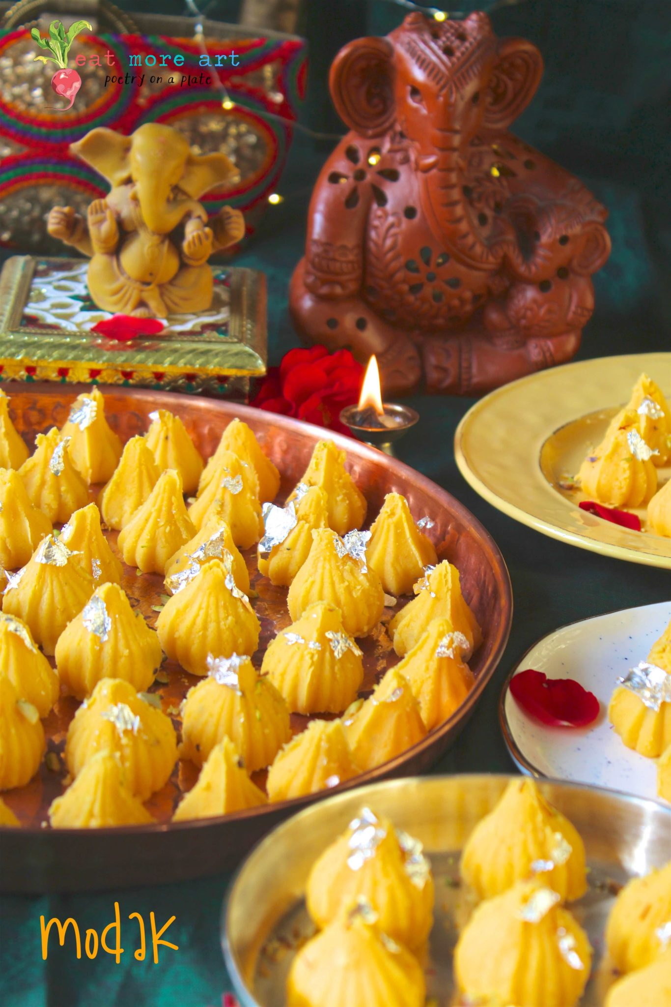 Yellow color modaks on a few different platters in front of Ganesh idol