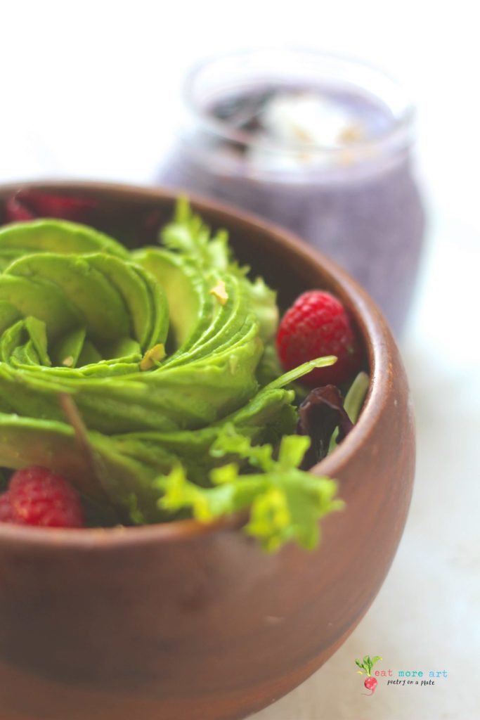 salad bowl topped with avocado rose and raspberries