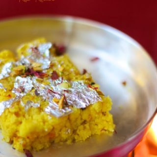 A side shot of saffron kalakand on a plate, garnished with dried rose petals and edible silver foil