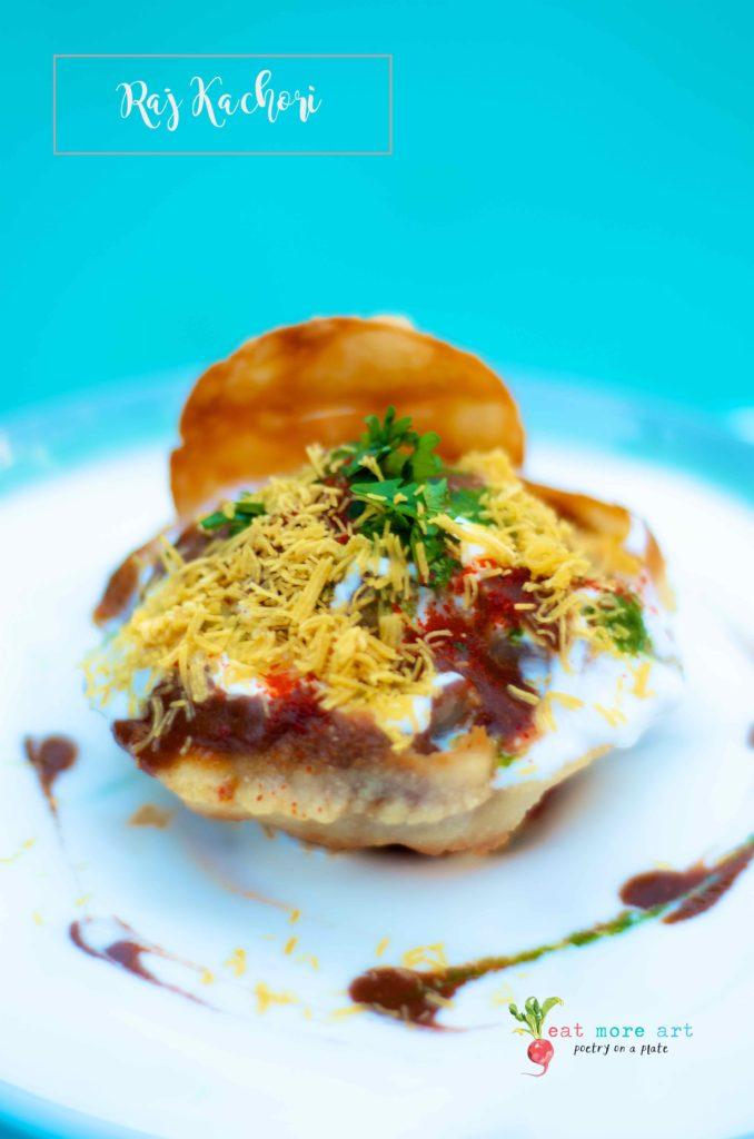 Raj Kachori drizzled with yogurt, chutneys, and garnished with sev and coriander