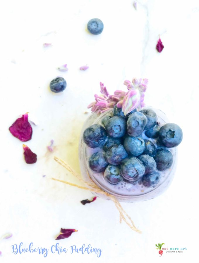 a top shot of a jar of blueberry chia pudding topped with blueberries and garnished with lavender and rose petals on the side