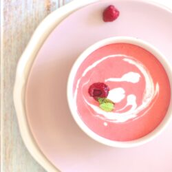An overhead shot of chilled raspberry dessert soup garnished with mint and heavy cream