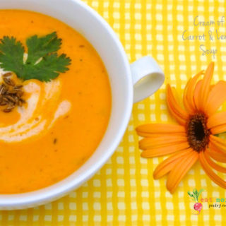 A cup of creamy carrot and lentil soup with a coriander garnish on top, with yellow backdrop and flower