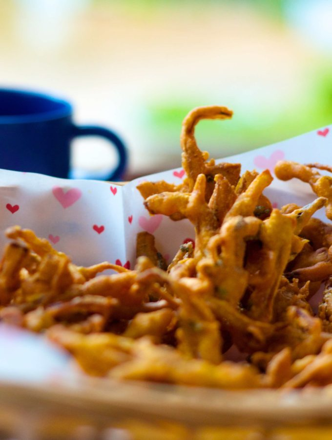 A close up of onion fritters in a basket lined with butter paper with hearts on it and a blue tea cup in background