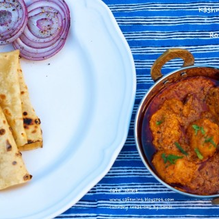 An overhead shot of Kashmir dum aloo in a copper vessel and roomali roti with onion roundels on a white plate on the side with a blue lined backdrop