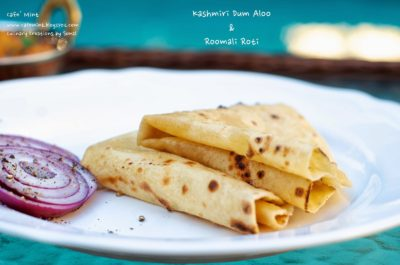 A side shot of roomali roti folded in triangle on a white plate