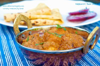 A side shot of kashmiri dum aloo in a copper utensil with folded roomali roti in background