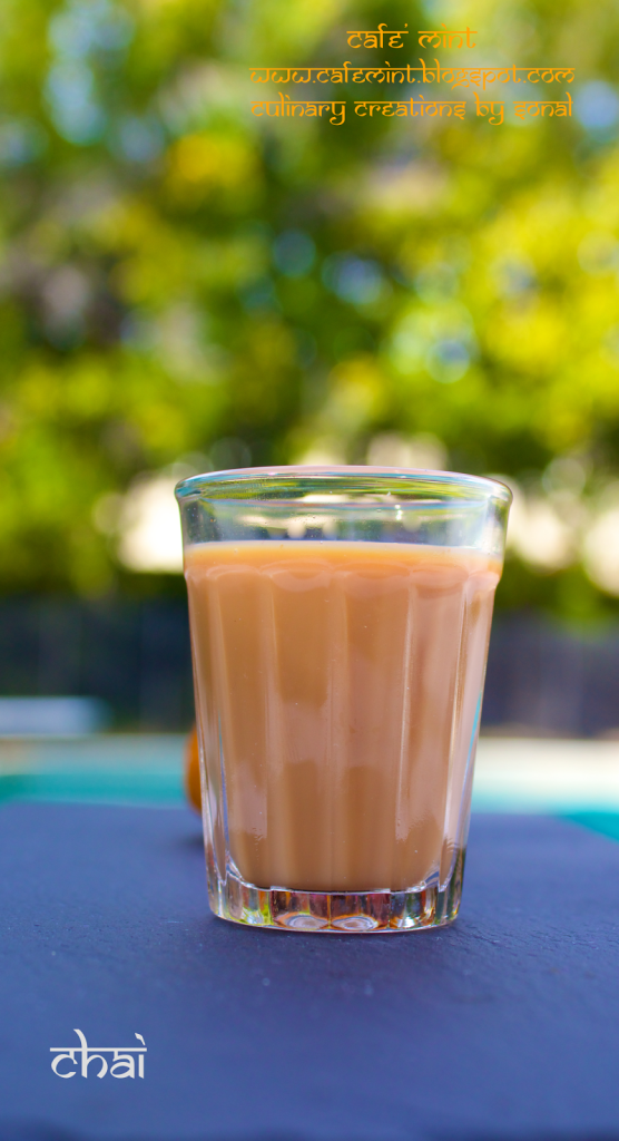 A side angle shot of a transparent glass filled with Indian masala tea