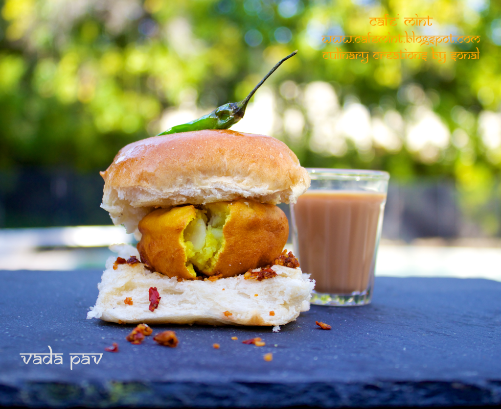 A vada pav with red chutney on a black plate with green chili on top and a glass of tea on the side