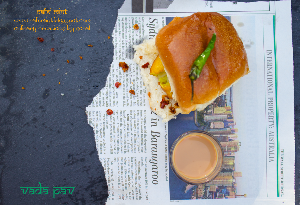 An overhead shot of vada pav with red chutney on a black plate with green chili on top and a glass of tea on the side served on a torn newspaper