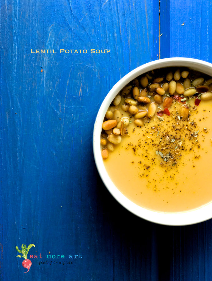 An overhead shot of a bowl of potato lentil soup garnished with pine nuts and oregano
