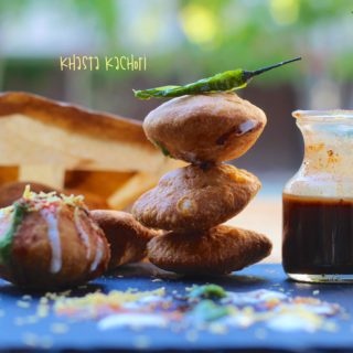 Khasta Kachori stacked up with green chili on top and chutney and khasta kachori chaat on the side