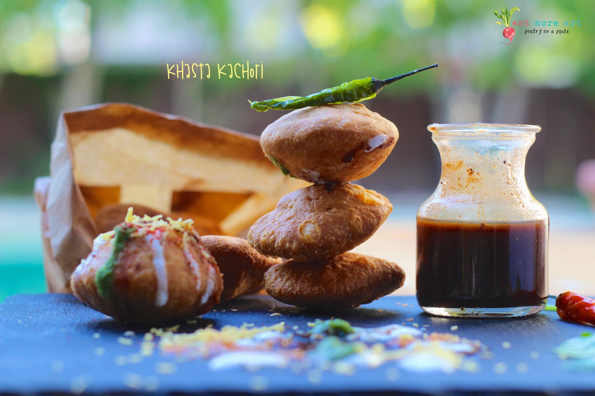 Khasta Kachori stacked up with green chili on top and chutney and khasta kachori chaat on the side