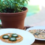 A plate of green spinach kofta with cut in half with white panner in center served with a side of roti with teal color pool background and a mint plant
