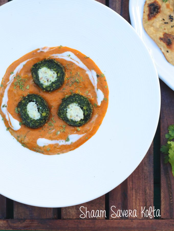 An overhead shot of plate of green spinach kofta with cut in half with white panner in center in orange color gravy served with a side of roti with teal color pool background