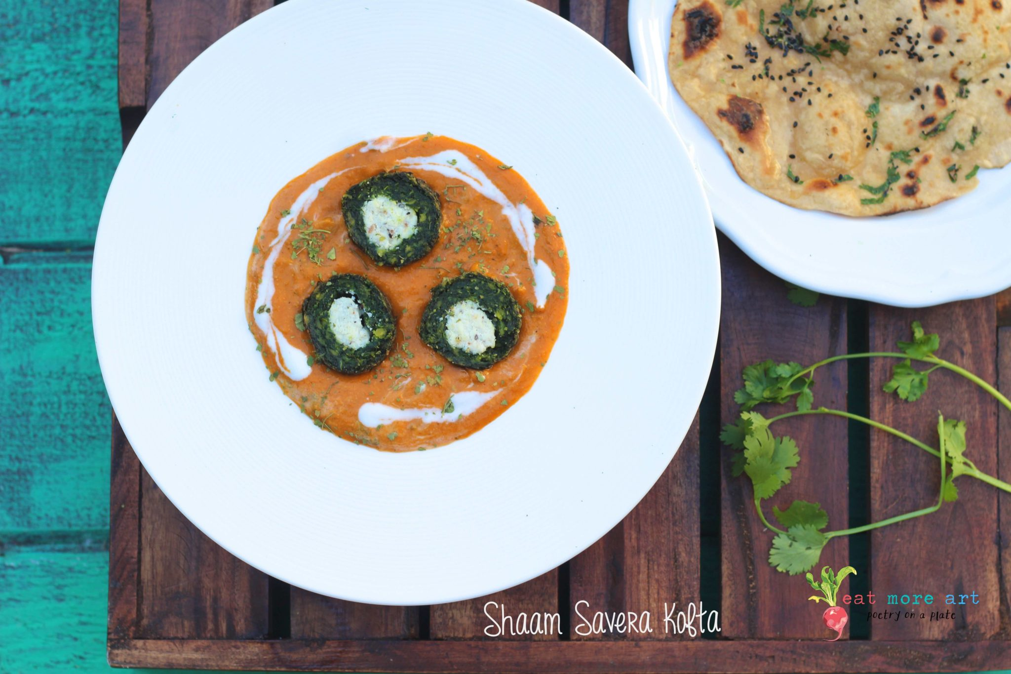 A overhaad shot of plate of green spinach kofta with cut in half with white panner in center in orange color gravy served with a side of roti with teal color pool background