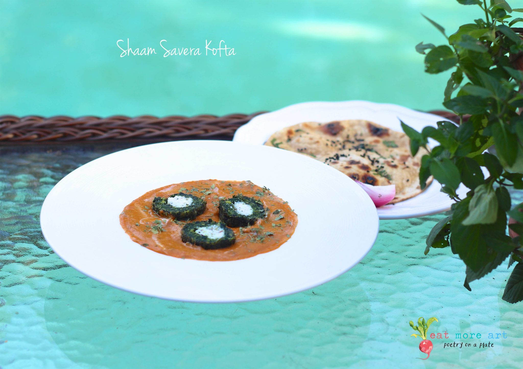A plate of green spinach kofta with cut in half with white panner in center served with a side of roti with teal color pool background
