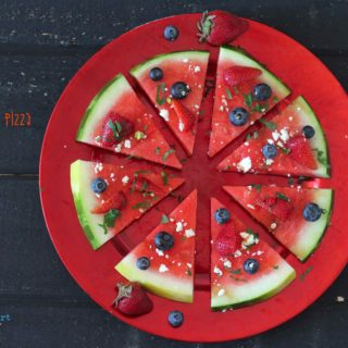 an overhead shot of Watermelon sliced like pizza topped with blueberries & strawberries feta cheese mint and balsamic vinegar on a red plate on black background
