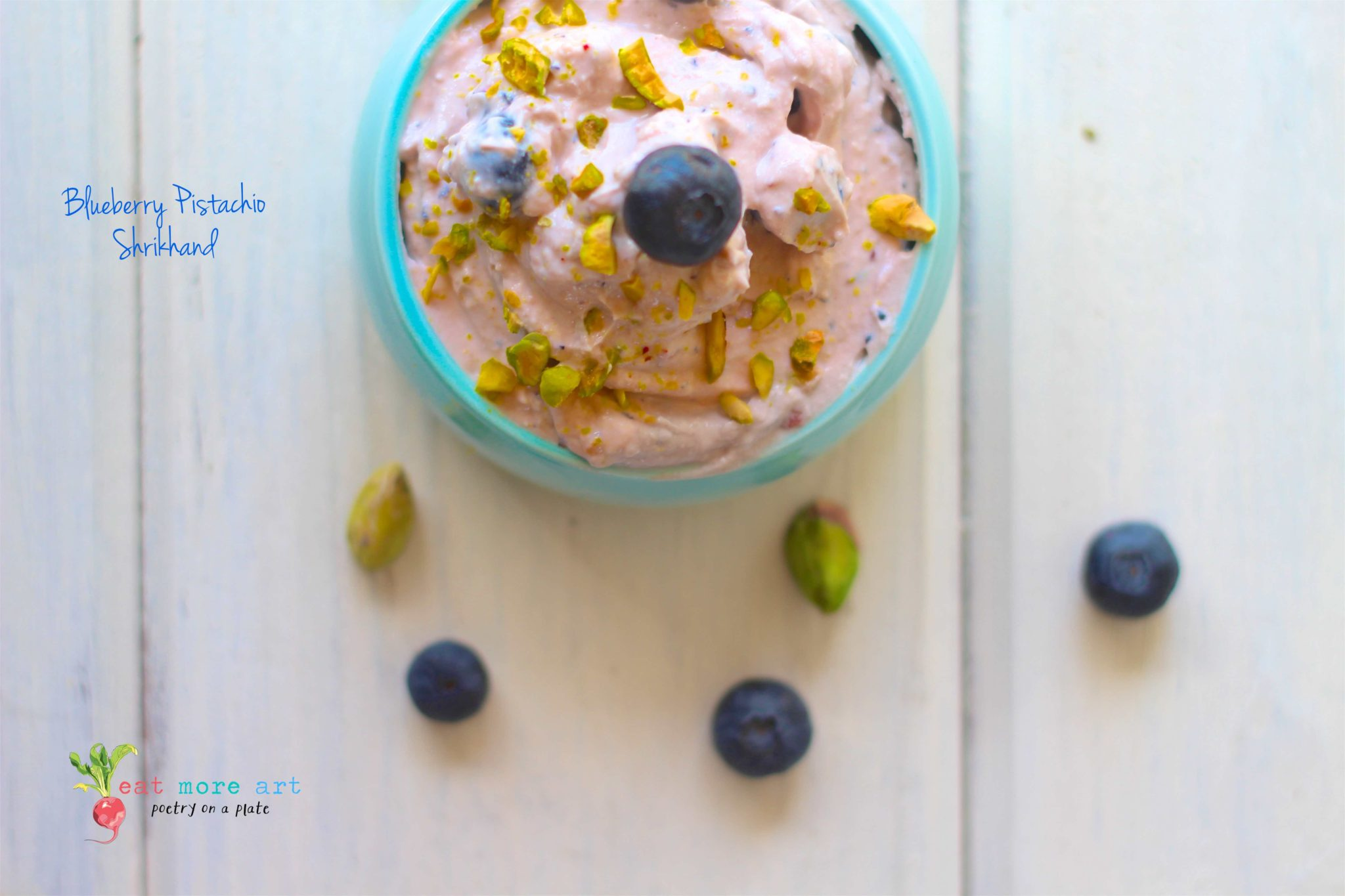 an overhead shot of lavender color Pistachio Blueberry Shrikhand served in a baby blue bowl on a white backdrop with pistachios and blueberries scattered around