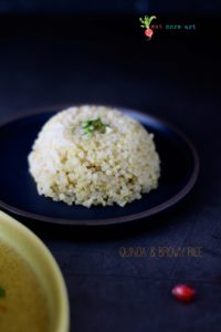 A side shot of quinoa and brown rice on black backdrop