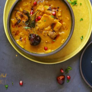 An overhead shot of dal dhokli in a black bowl on yellow platter with a side of rice and quinoa