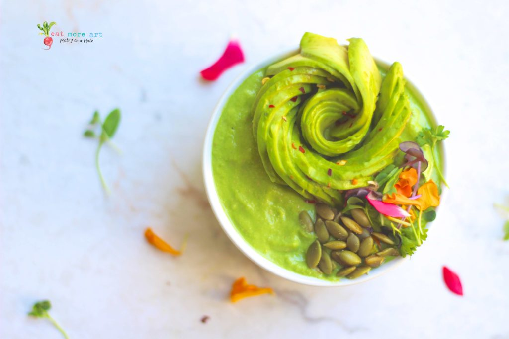 green smoothie bowl topped with avocado rose and edible flowers