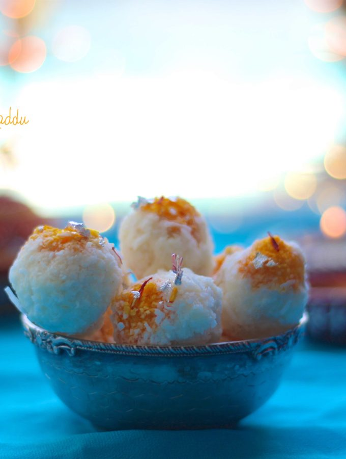 A side shot of coconut laddu in a bowl, with teal background and lights with bokeh effect