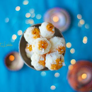 An overhead shot of coconut laddu in a bowl, with teal background and lights with bokeh effect