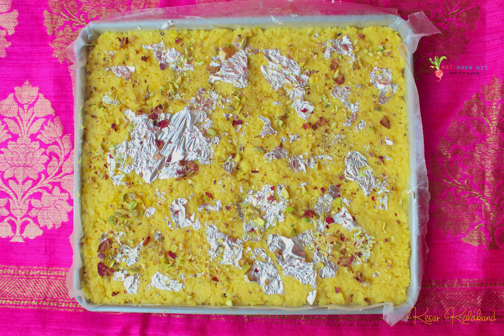 An overhead shot of saffron kalakand on a plate, garnished with dried rose petals and edible silver foil