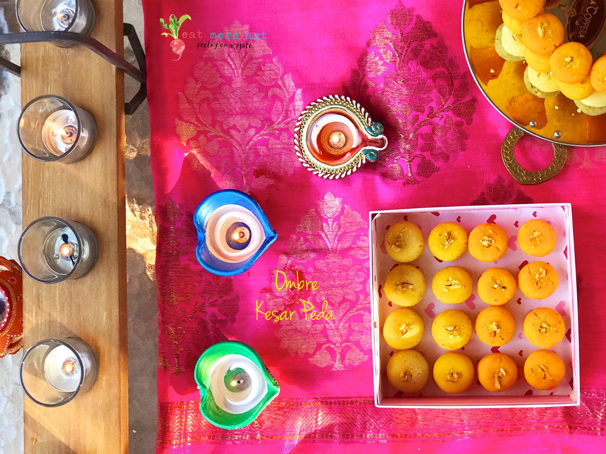 Ombre saffron peda in shades of yellow and orange arranged in a box on a hot pink background surrounded by tea lights