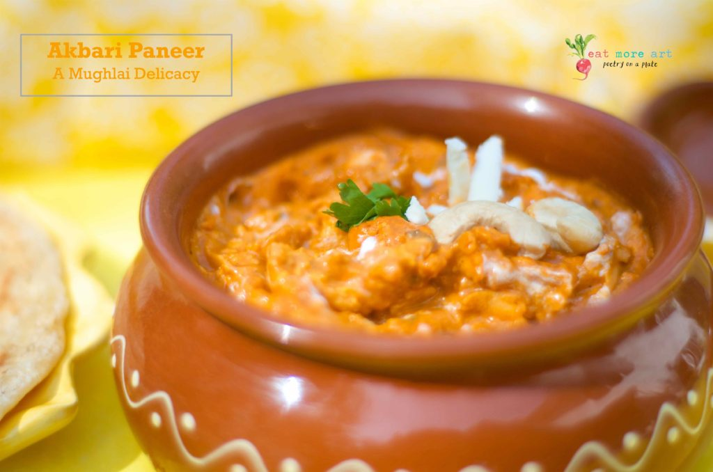 A side shot of the Akbari Paneer garnished with paneer, cashews, and coriander leaf, in a clay pot