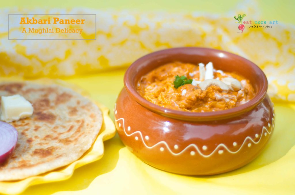 A side shot of the Akbari Paneer garnished with paneer, cashews, and coriander leaf, in a clay pot, served with Paratha on the side