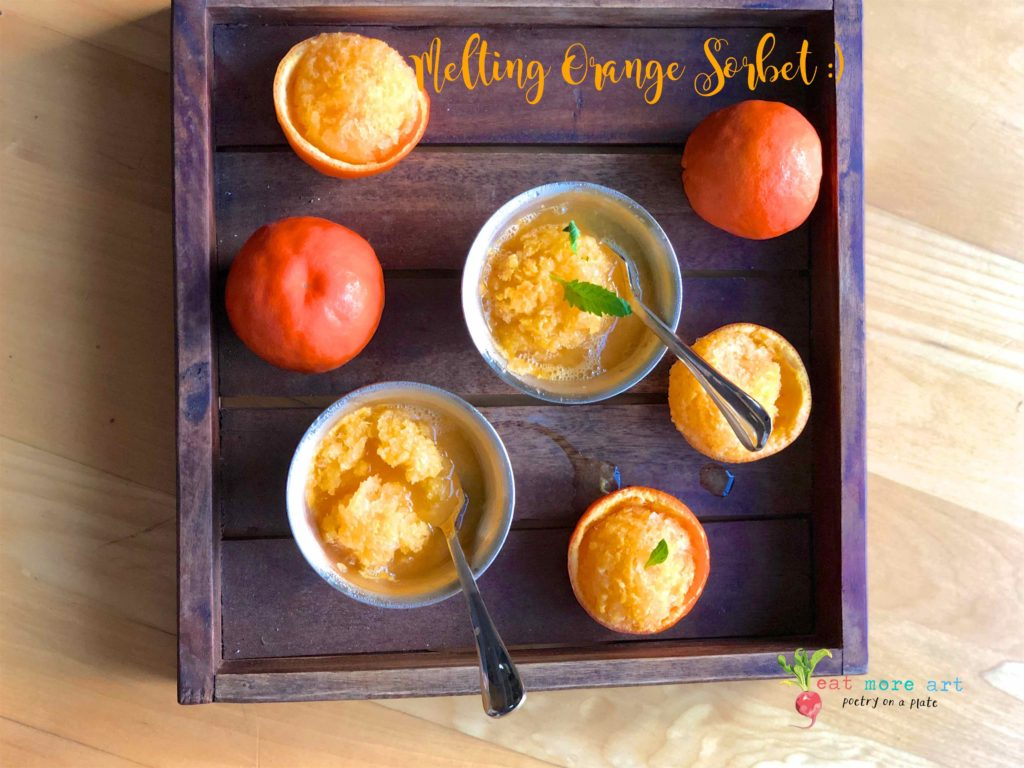 an overhead shot of melting orange sorbet bowls on a tray, with a couple of oranges.