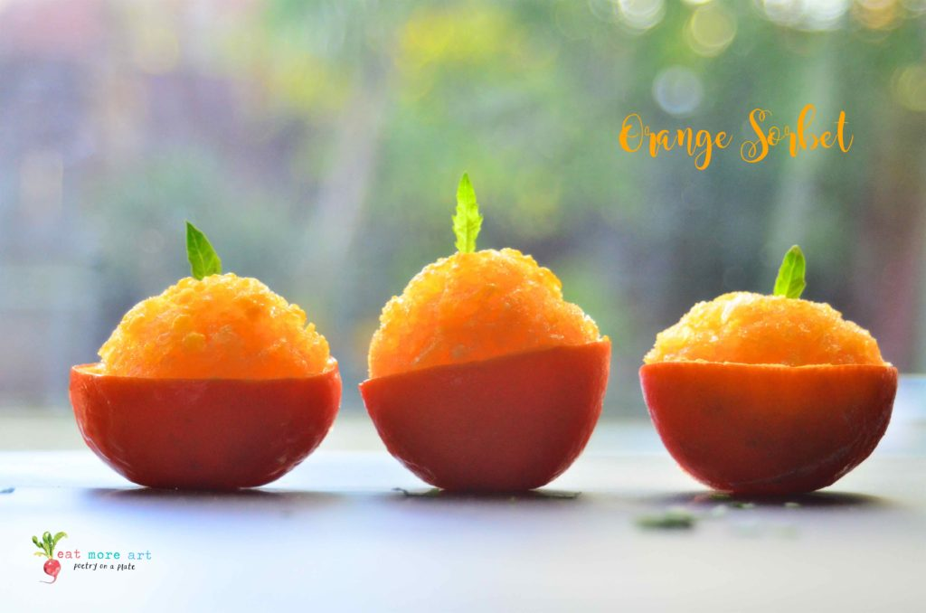 a side shot of orange sorbet served in orange peel bowls, garnished with mint