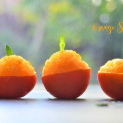 a side shot of orange sorbet served in orange peel bowls, garnished with mint