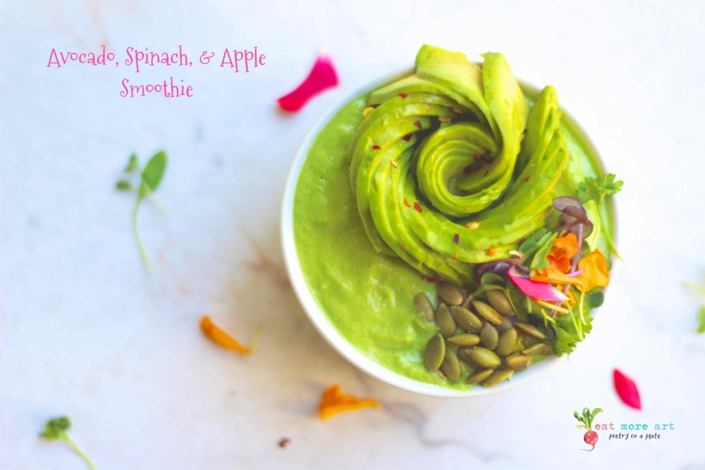 An overhead shot of avocado spinach apple smoothie garnished with avocado rose, edible flowers, and sunflower seeds