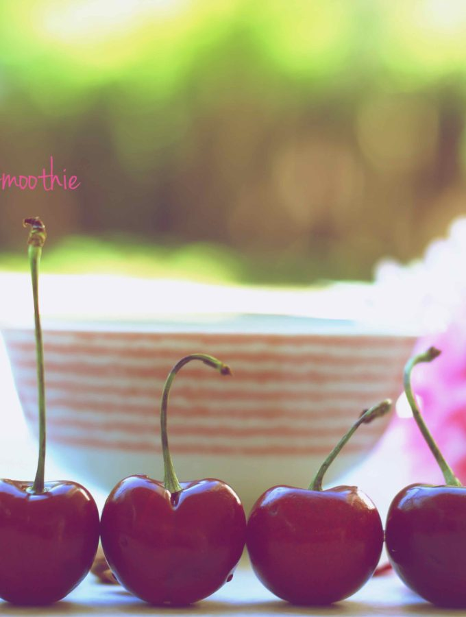 A close up shot of 5 cherries in a line, with smoothie bowl in the background