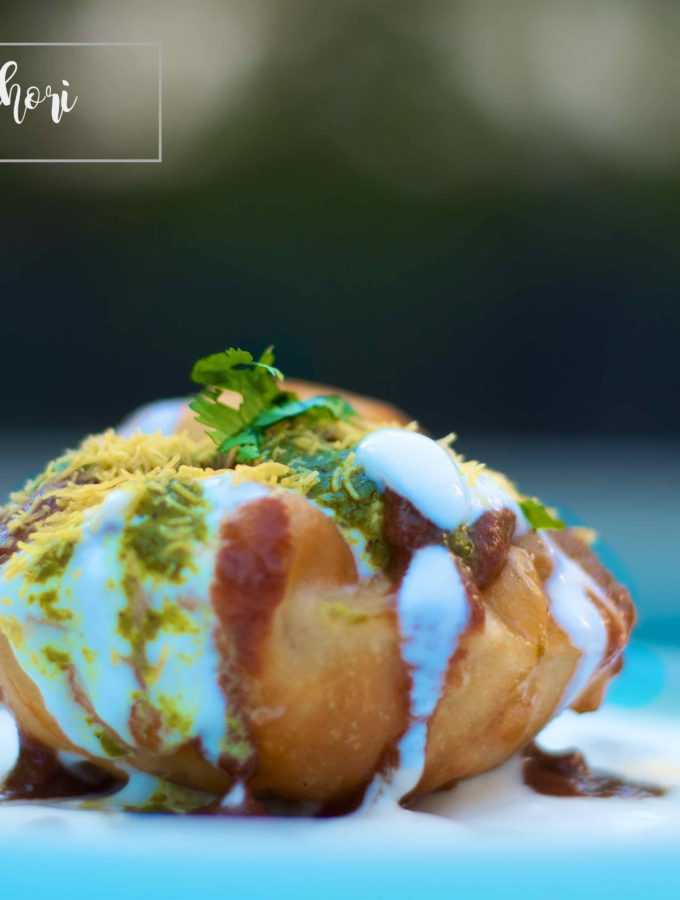 Raj Kachori drizzled with yogurt, chutneys, and garnished with sev and coriander