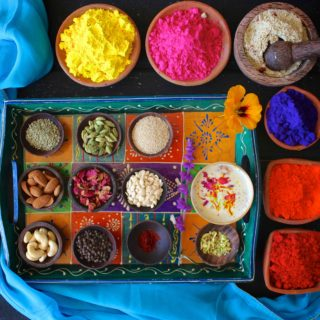 An overhead shot of a colorful tray of thandai, it's ingredients, and holi colors