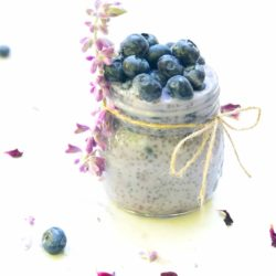 Side shot of a jar of blueberry chia pudding topped with blueberries and garnished with lavender and rose petals on the side
