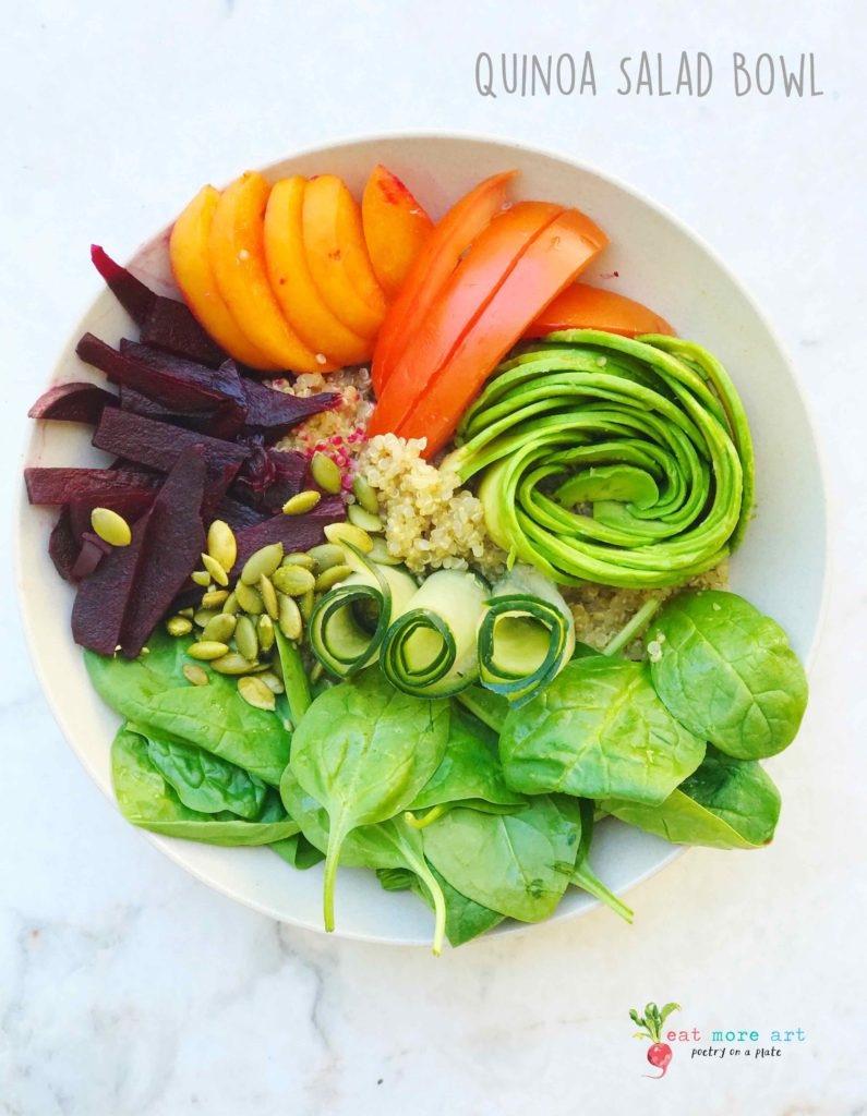 An overhead shot of vegan quinoa salad bowl with fruits and veggies