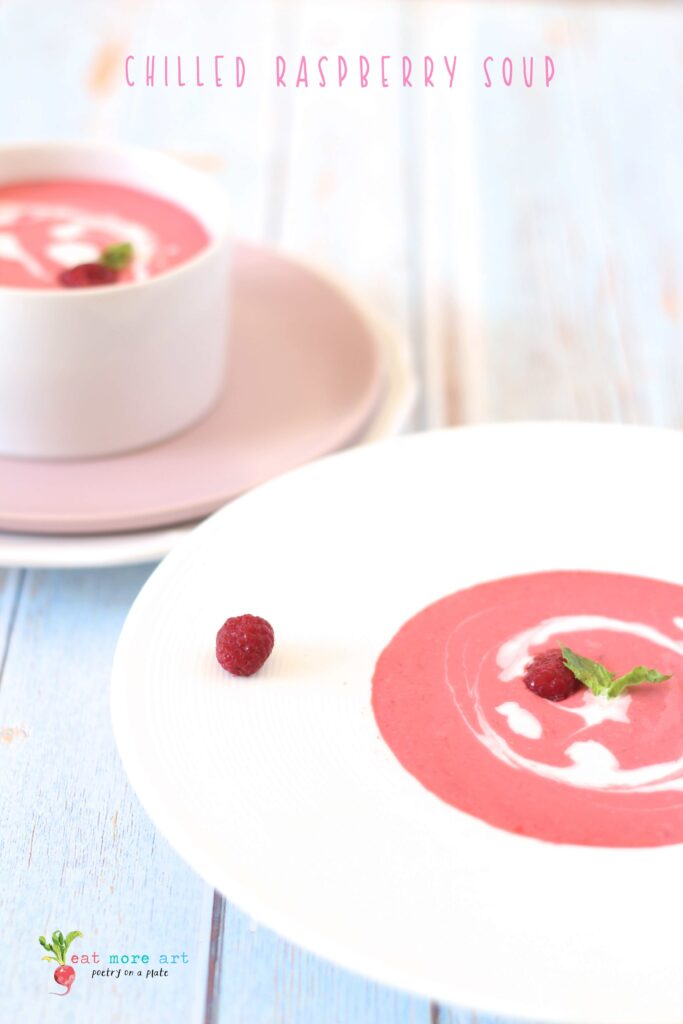 A side shot of chilled raspberry dessert soup garnished with mint and heavy cream