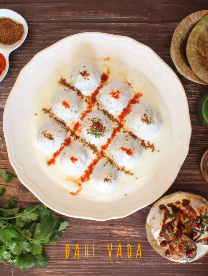 A horizontal overhead flat lay shot of dahi vada with condiments on the side