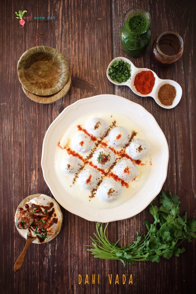 A vertical overhead flat lay shot of dahi vada with condiments on the side