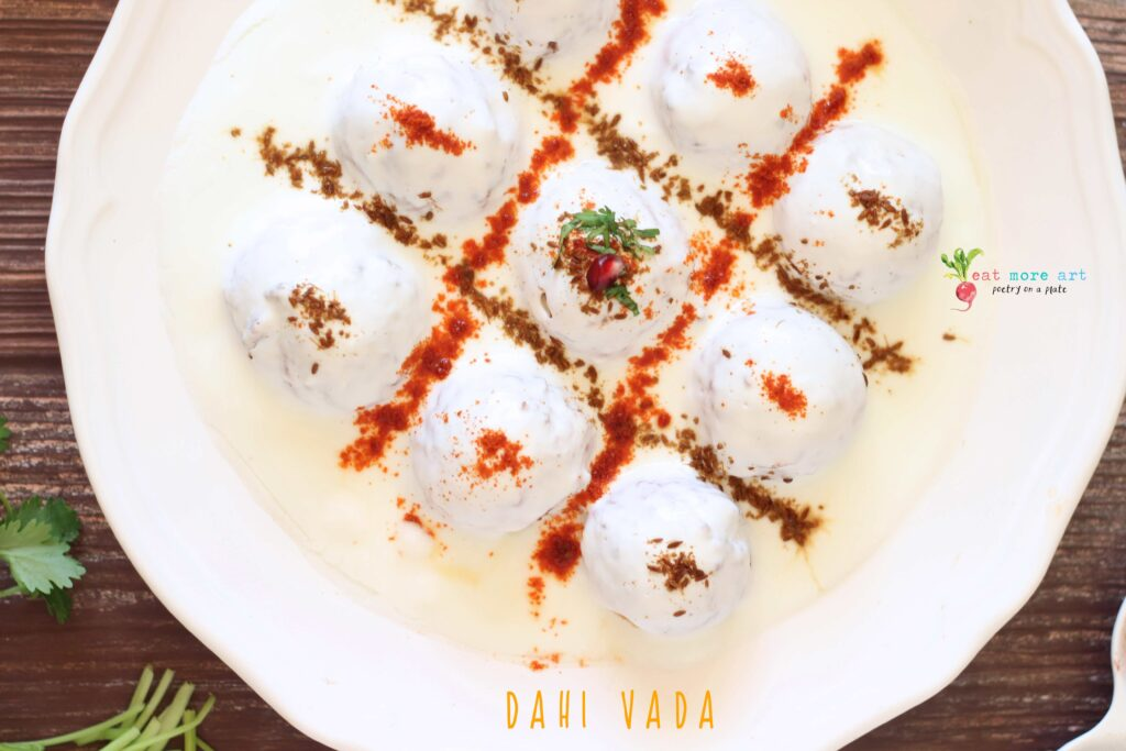 An overhead closeup shot of dahi vada garnished with cumin and chili powder