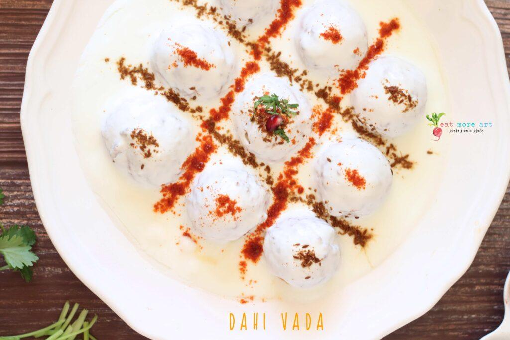 An overhead closeup shot of dahi vada garnished with cumin and chili powder